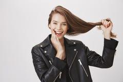Les cheveux sont forts comme elle-même Portrait de l'amie européenne heureuse émotive tirant les cheveux de côté et le visage émo Image stock