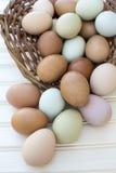 Les chickeneggs organiques frais débordent hors du panier sur le backg en bois Image stock