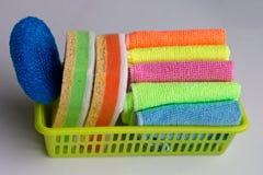 Les chiffons et les éponges colorés sont dans le panier photo stock