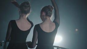 Les chiffres de la danse professionnelle mince de deux ballerines dans la robe noire dans le studio devant des rayons d'un projec banque de vidéos
