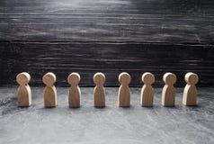 Les chiffres en bois des personnes se tiennent dans une rangée et attendent Les gens dans la formation Ressources humaines, la re Image libre de droits