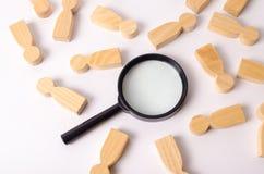 Les chiffres en bois des personnes se trouvent autour d'une loupe sur un fond blanc Louant pour le travail, personnes de découver Photographie stock