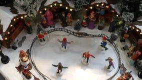 Les chiffres miniatures de patin sur une patinoire congelée et à l'arrière-plan est le marché de Noël banque de vidéos