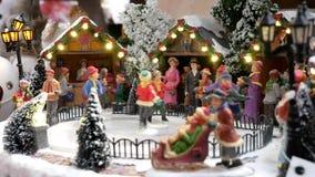 Les chiffres miniatures de patin sur une piste de patinage d'hiver et à l'arrière-plan est le marché de Noël clips vidéos