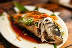 Les chinois traditionnels que les plats du village sont Dazhay ont cuit des poissons à la vapeur avec la sauce de soja et les lég image libre de droits
