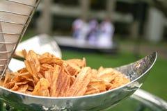 Les chips doux de banane comme casse-croûte sont plaque d'acier inoxydable maintenue en partie image libre de droits