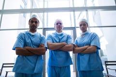 Les chirurgiens avec des bras ont croisé la position dans le couloir d'hôpital Photographie stock libre de droits