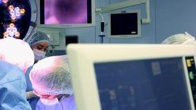 Les chirurgiens et les assistants professionnels parlent et ont utilis? l'ordinateur pendant la chirurgie Ils fonctionnent dans l banque de vidéos