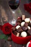 Les chocolats dans une boîte en forme de coeur et un groupe de roses rouges courtisent dessus Photographie stock libre de droits