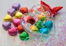 Les chocolats en forme de coeur de Valentine enveloppés dedans enveloppés en couleurs Image stock