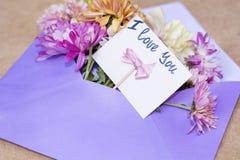 Les chrysanthèmes fleurit dans l'enveloppe violette avec je t'aime la carte Photos stock