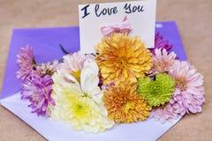 Les chrysanthèmes fleurit dans l'enveloppe violette avec je t'aime la carte Image libre de droits