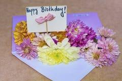 Les chrysanthèmes fleurit dans l'enveloppe violette avec la carte de joyeux anniversaire d'I Image stock