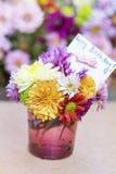 Les chrysanthèmes fleurit dans le vase en verre pourpre avec la carte de joyeux anniversaire Image libre de droits