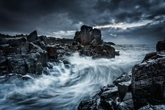 Les cieux dramatiques déprimés et les grandes vagues se brisent sur les roches côtières image libre de droits