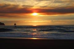 Les cieux nuageux et le coucher du soleil au-dessus de l'Orégon marchent les affleurements rocheux de l'océan pacifique Image libre de droits