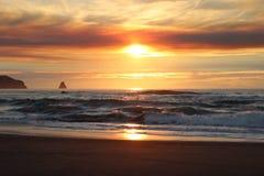 Les cieux nuageux et le coucher du soleil au-dessus de l'Orégon marchent les affleurements rocheux de l'océan pacifique Images libres de droits