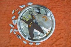 Les ciseaux antiques énormes en métal et une bouteille blanche se trouvent sur un plat rond sur un fond orange, entouré par un pe Photo stock