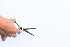 Les ciseaux des cheveux dans l'isolat de mains sur le fond Image stock