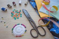 Les ciseaux et le kit de couture incluent des fils de différentes couleurs, de dé et d'autres accessoires de couture sur la table Photographie stock