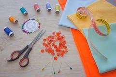 Les ciseaux et le kit de couture incluent des fils de différentes couleurs, de dé et d'autres accessoires de couture sur la table Image stock