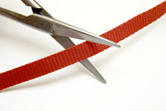 Les ciseaux ont coupé la bande rouge Image stock