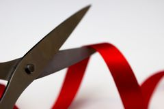 Les ciseaux pointus ont coupé le ruban rouge de satin Image stock