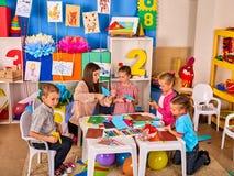 Les ciseaux préscolaires dans les enfants remettent le papier de coupe avec le techer dans la classe Photos libres de droits