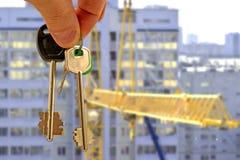 Les clés à l'appartement à disposition sur le fond des maisons Photos stock