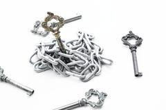 Les clés de vintage ont mis dans la chaîne de fer, entourant avec d'autres clés sur le fond blanc Photographie stock