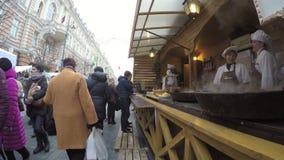Les clients achètent la nourriture fraîchement cuite au four du cuisinier dans la tente extérieure banque de vidéos