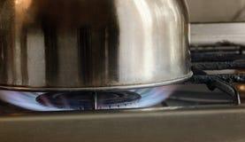 Les coûts brillants d'articles de cuisine en métal sur le gaz allumé incendient photographie stock libre de droits