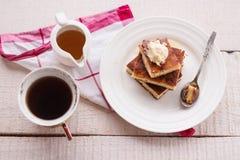 Les cocottes en terre de morceaux d'un plat rond et d'une crème, café de tasse, versent le miel Photographie stock