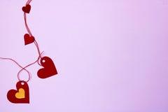Les coeurs accrochants se sont reliés par une corde et peu là, fond violet doux Photos libres de droits