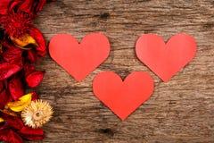 Les coeurs avec le pot-pourri rouge fleurissent des pétales sur le fond en bois Image stock
