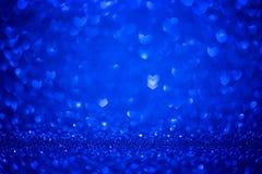 Les coeurs bleus de forme de Bokeh aiment le fond de jour avec les lumières bleues lumineuses de scintillement pour la Saint-Vale photos libres de droits