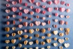 Les coeurs colorés empaquettent la guirlande accrochant sur le mur Fond romantique de Saint-Valentin Photos libres de droits