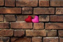 Les coeurs de Knit rouges et roses se tiennent sur un vieux Br rouge de émiettage Image stock