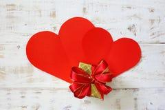 Les coeurs de papier rouges copient l'espace avec le boîte-cadeau sur le blanc Image libre de droits