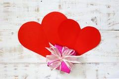 Les coeurs de papier rouges copient l'espace avec le boîte-cadeau sur le bois blanc de vintage Photographie stock