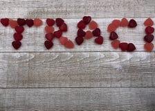 Les coeurs de sucrerie orthographient le nom TRACI sur le fond gris de conseil Photographie stock