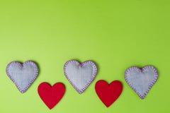 Les coeurs de Valentine des jeans et le rouge se sont sentis sur le fond coloré de verdure Vue supérieure Copiez l'espace pour le Photo stock