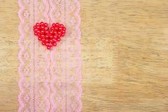 Les coeurs de Valentine sur la dentelle modèlent le tissu, fond en bois Photographie stock