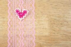 Les coeurs de Valentine sur la dentelle modèlent le tissu, fond en bois Image libre de droits