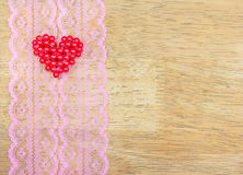Les coeurs de Valentine sur la dentelle modèlent le tissu, fond en bois Images libres de droits