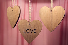 Les coeurs en bois de jour de valentines avec le mot aiment sur le fond rose Images stock