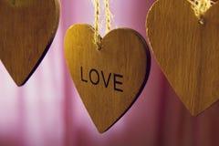 Les coeurs en bois de jour de valentines avec le mot aiment sur le fond rose Images libres de droits