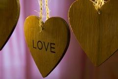 Les coeurs en bois de jour de valentines avec le mot aiment sur le fond rose Photo stock