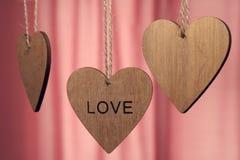 Les coeurs en bois de jour de valentines avec le mot aiment sur le fond rose Image stock