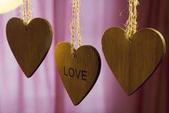 Les coeurs en bois de jour de valentines avec le mot aiment sur le fond rose Photos libres de droits